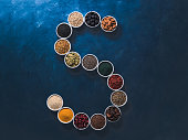 Above view of various superfoods in smal bowl in form S letter on dark blue background. Superfood as chia,spirulina,cocoa bean,goji, hemp, blueberry, quinoa, bee pollen,black sesame,turmeric. Top view