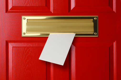 A mail slot in a red door.