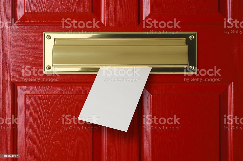 Letter sliding through brass mail slot on a red door stock photo
