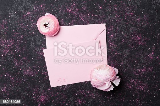 825251738istockphoto Letter with paper blank decorated ranunculus flowers. Wedding mockup or greeting card on mother day in flat lay styling. 680464086