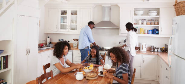 letterbox format shot of family using digital devices at home - eating technology stock photos and pictures