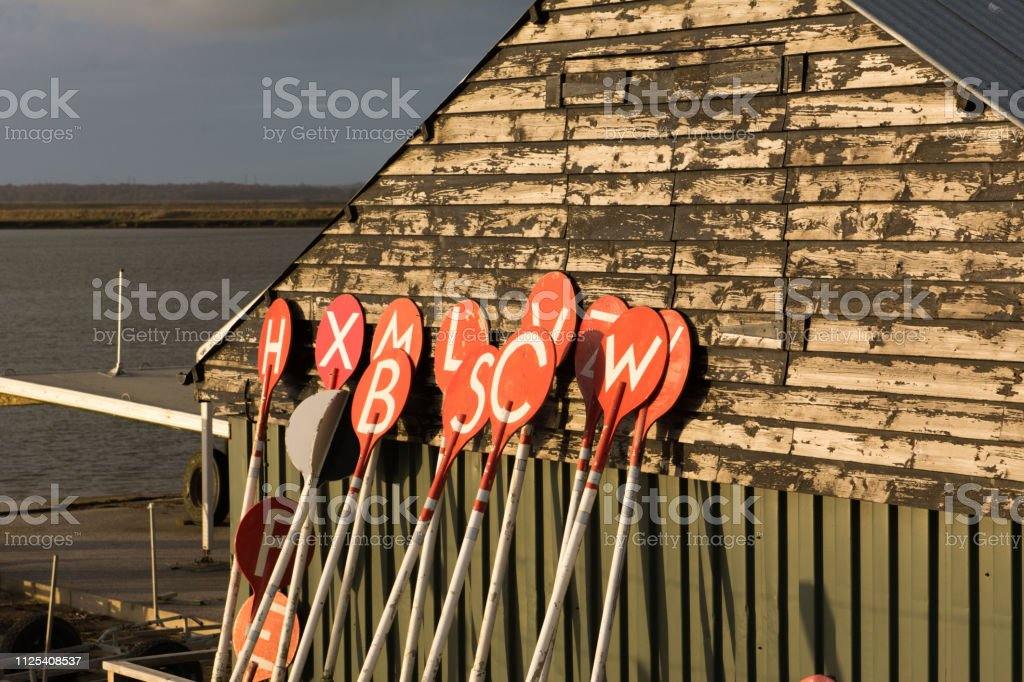 Lettered bouy markers leaning against fishing hut stock photo