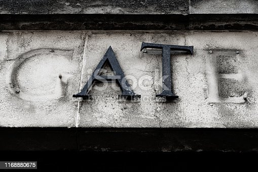 Letters 'A' and 'T' on the facade of an abandoned office building.  These are all that remain of the word 'gate'.  Belfast, Northern Ireland.