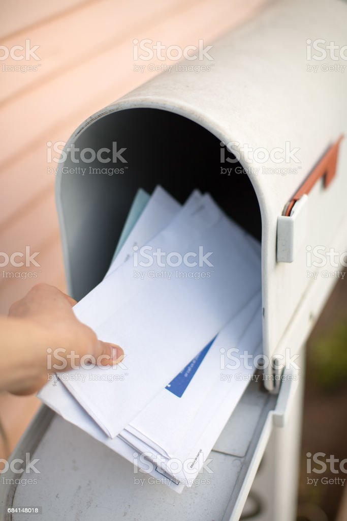 Letters in a mailbox are being held by a hand. stock photo