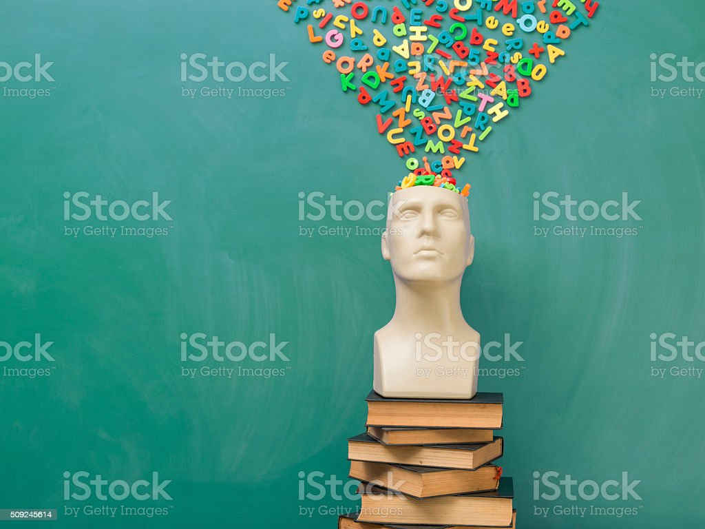 Letters in plastic mannequin head over green chlakboard stock photo