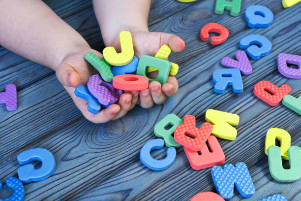 Letters of the English alphabet in the hands of a child on a wooden background. stock photo