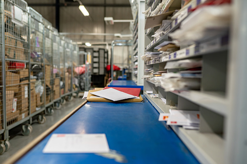 Letters on a sorting frame, table and shelves in a mail delivery sorting centre. Postal service, post office inside