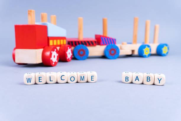"""buchstaben mit der aufschrift """"welcome baby"""" vorne, ein bunter spielzeugzug im rücken - neugeborenes-konzept - geschenk zur taufe stock-fotos und bilder"""