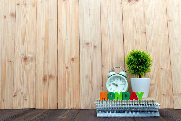 monday letters text and notebook paper, alarm clock and little decoration tree in white vase on wooden background, hello monday concept. - monday motivation stock photos and pictures