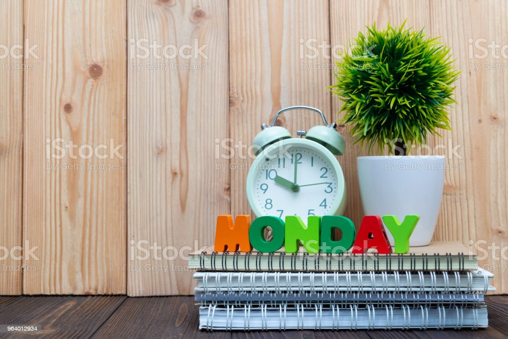 MONDAY letters text and notebook paper, alarm clock and little decoration tree in white vase on wooden background, hello Monday concept. - Royalty-free Business Stock Photo