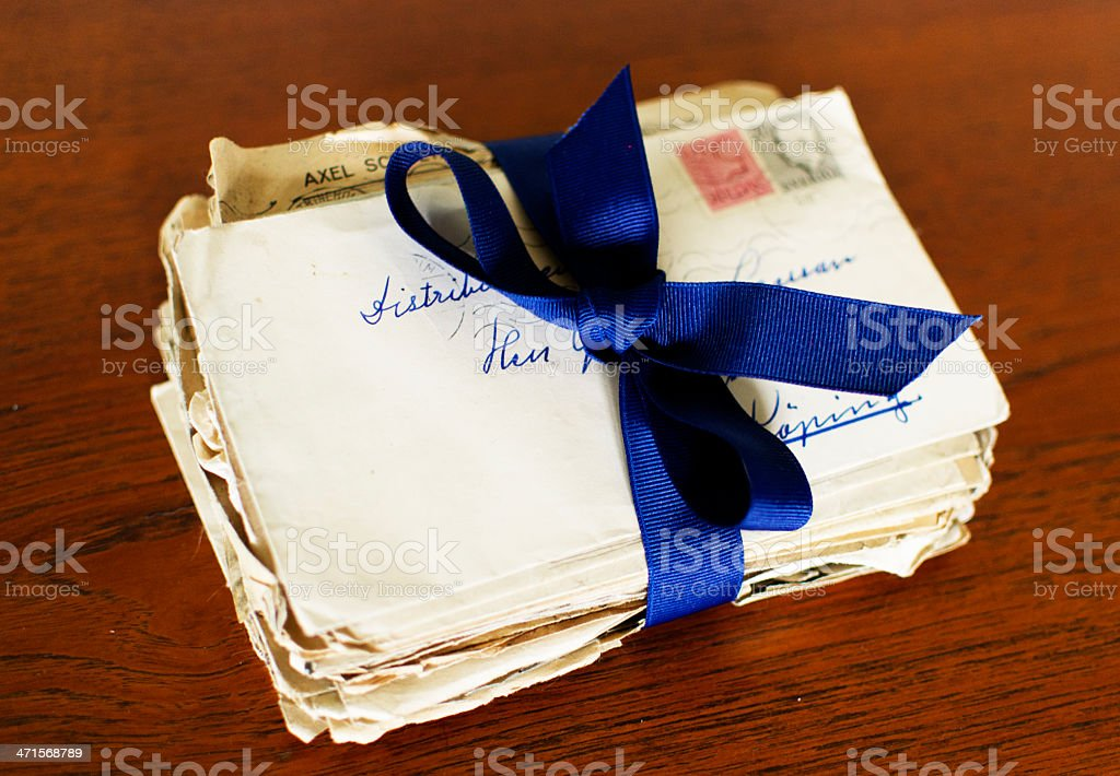 Letters tied together with ribbon A stack of old correspondence tied together with a blue ribbon, lie on an old oak desk.  Application Form Stock Photo