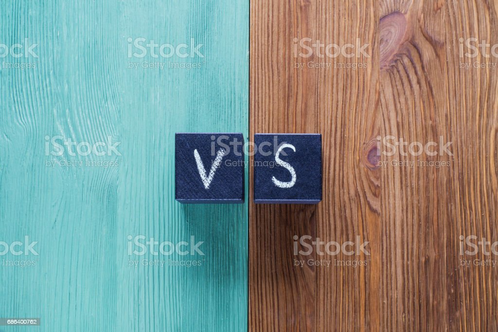 Letters VS on wooden background with copy space. Letters VS on wooden background with copy space. The concept of making choice.  Versus letters. Turquoise and brown wooden background and black cubes with letters VS. Abstract Stock Photo