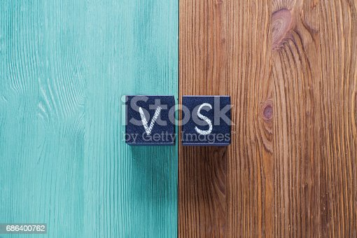 istock Letters VS on wooden background with copy space. 686400762