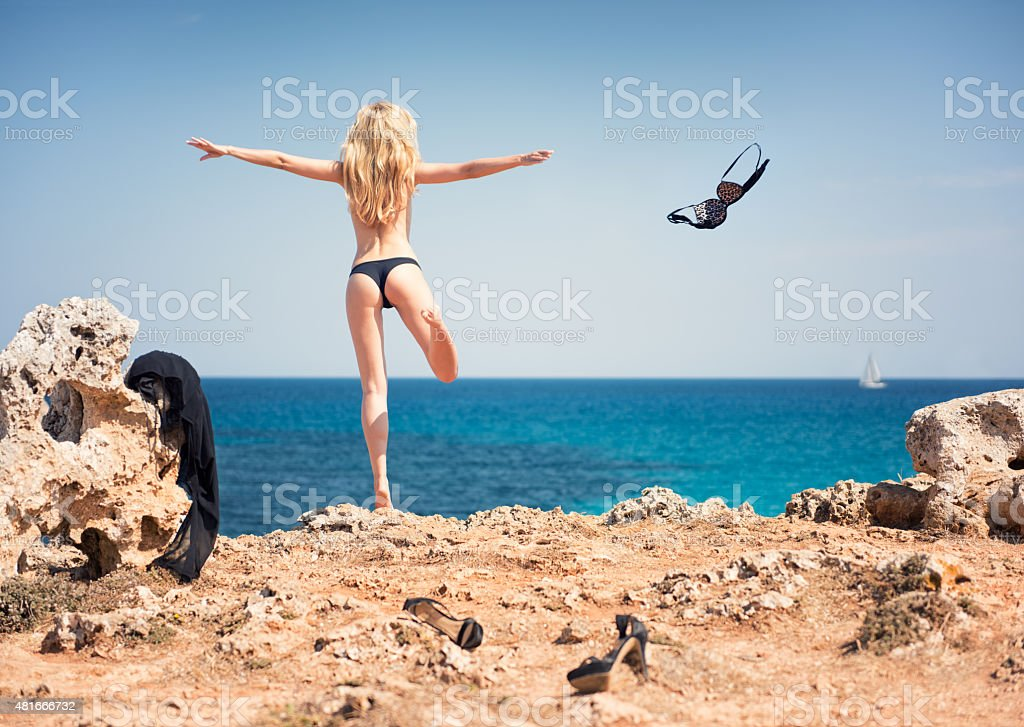Letting go, Girl Skinny Dipping throwing away her clothes stock photo
