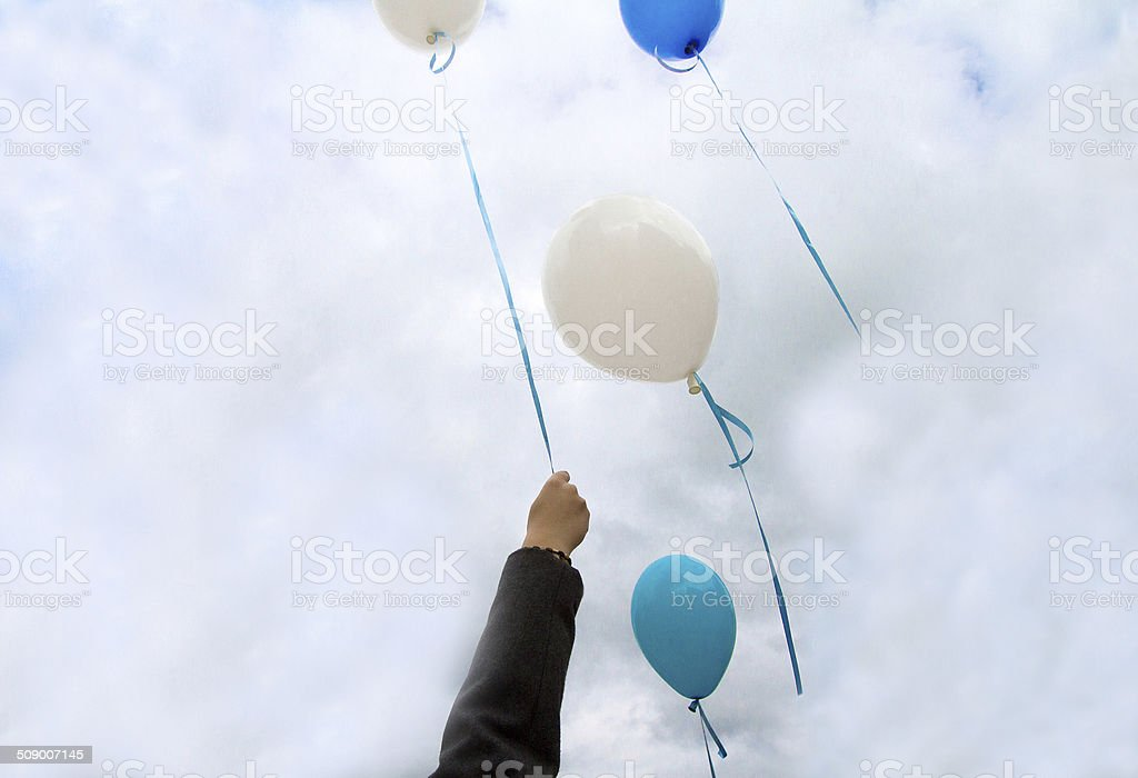 Letting Go: Hand Ready to Release the Last Balloon stock photo