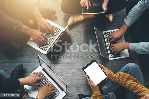 Shot of a group of unrecognizable employees using different devices inside