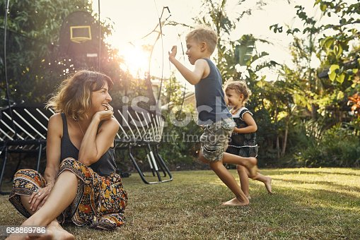Shot of a young mother hanging outside with her son and daughter