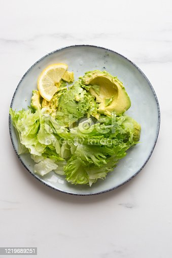 lettuce and avocado in rustic plate on white marble background