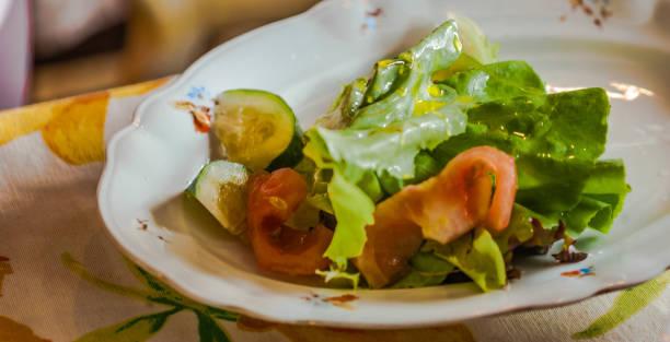 Salada de alface, pepino e tomate temperado com azeite de oliva. Foco seletivo. - foto de acervo