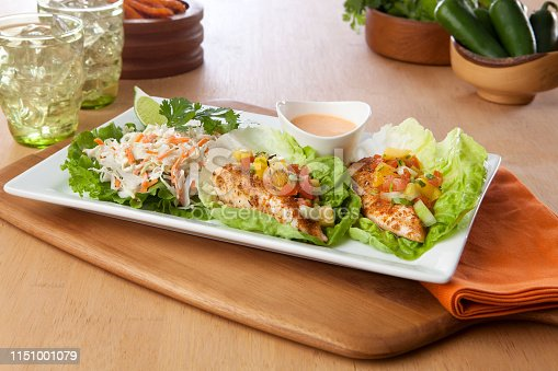 two lettuce wrap fish tacos on a platter with drinks