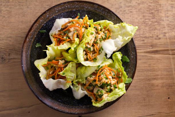 lettuce wraps with chicken, carrot, peanuts and scallion. stuffed iceberg lettuce leaves with chicken - wrapping paper stock photos and pictures