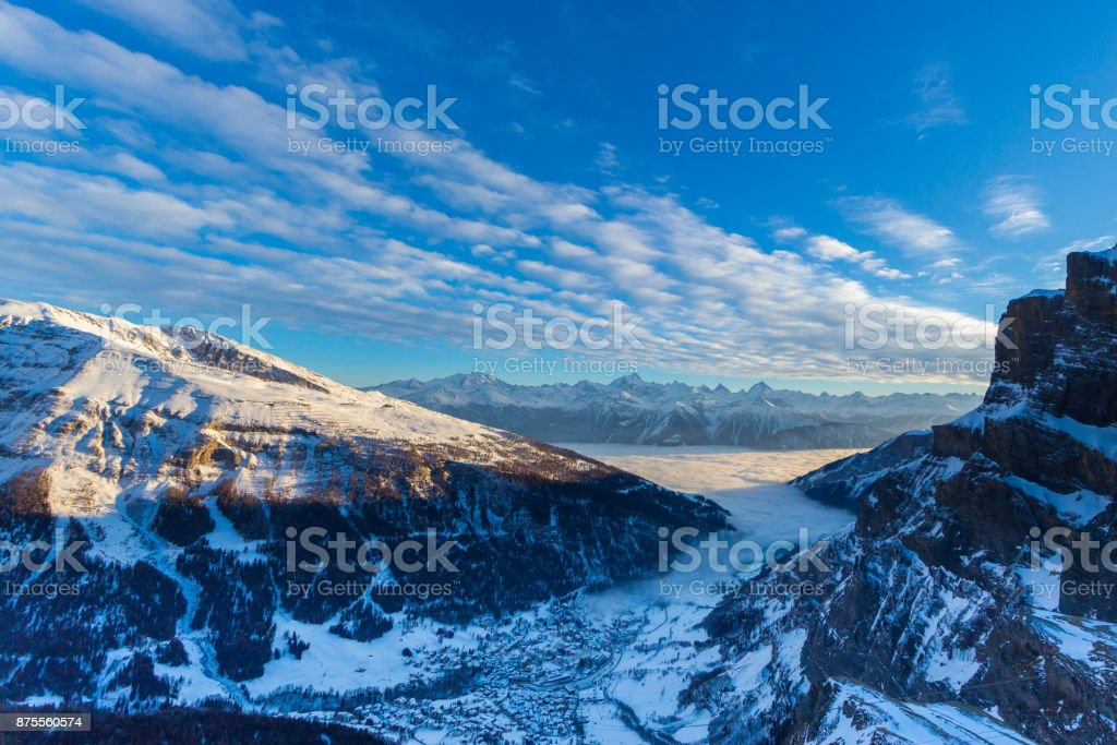 Leukerbad view from Gemmi pass in evening sun, snow, sea of fog stock photo