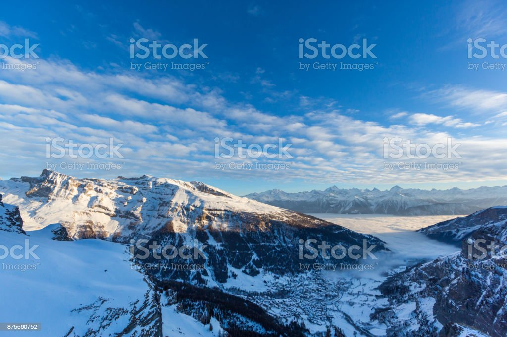 Leukerbad view from Gemmipass, evening sun, sea of fog, winter, snow stock photo
