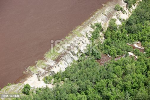 A levee breached by muddy floodwater following a storm. A lake is to the left and wooded area to the right. Shot from the open window of a small plane.