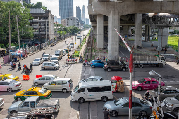 level crossing and road junction in bangkok, thailand - motorbike, umbrella stock photos and pictures