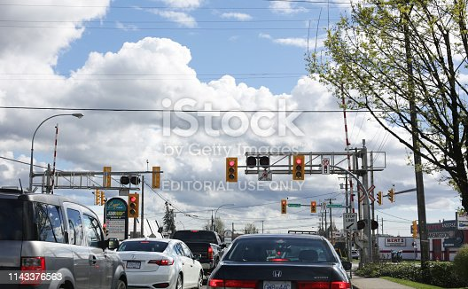 Langley, Canada - April 7, 2019: Traffic stops at the level crossing on 200 Street and Production Way in Langley City. Spring afternoon in Metro Vancouver.