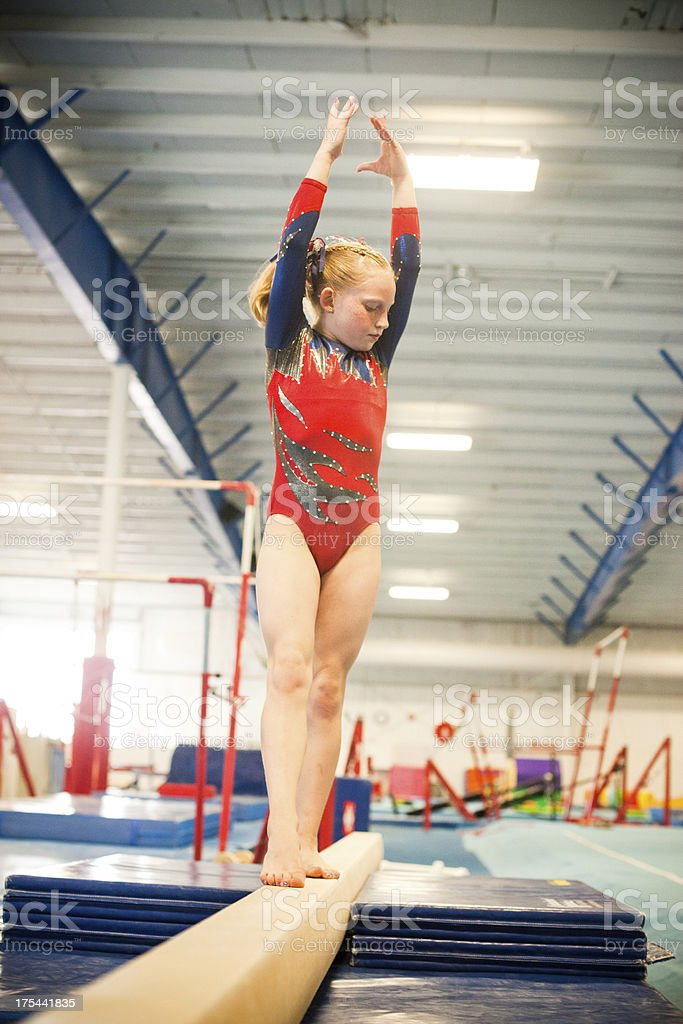 Level five gymnast practicing on beam. stock photo
