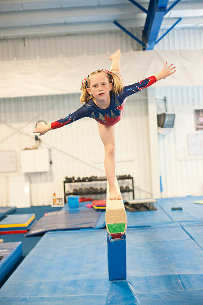 level five gymnast practicing on beam. - uneven parallel bars stock photos and pictures