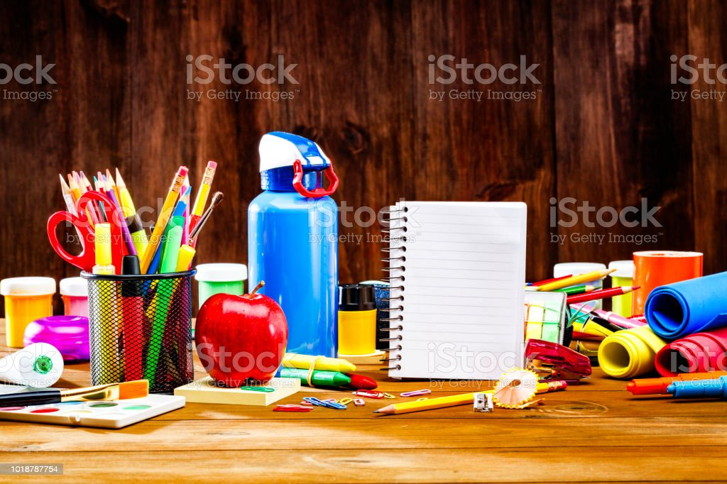 Level view of back to school office supplies on wooden table with apple snack and note book stock photo