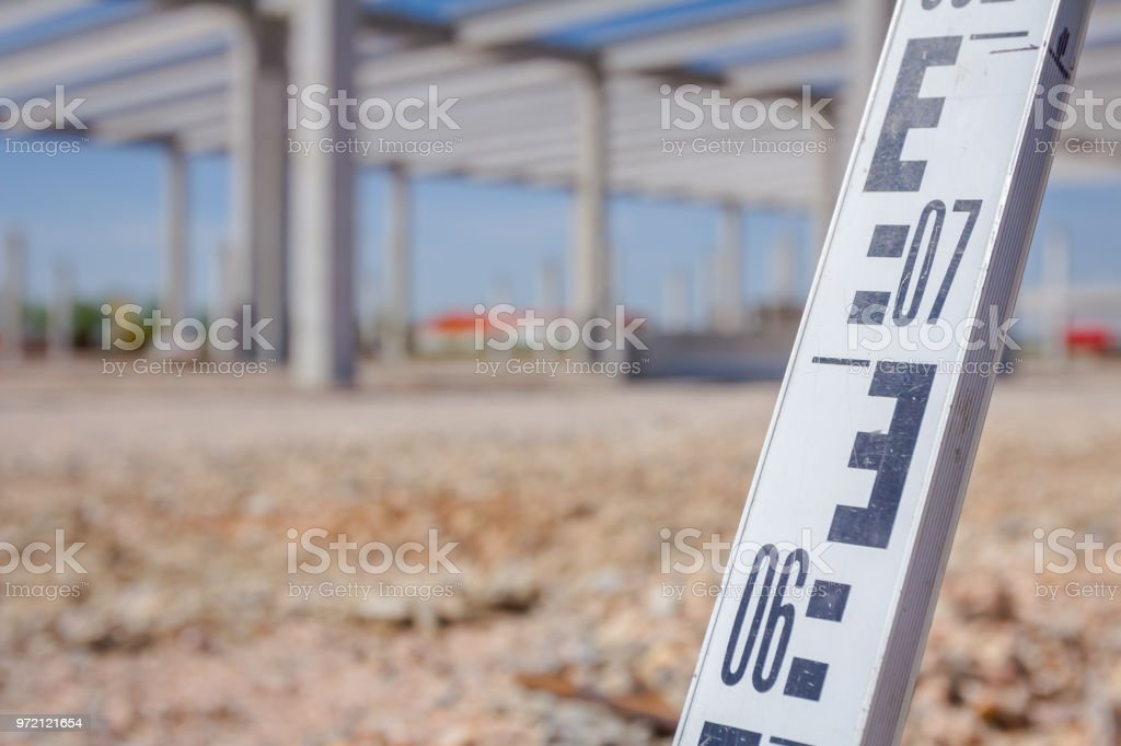 Leveling rod for measuring level on construction site stock photo