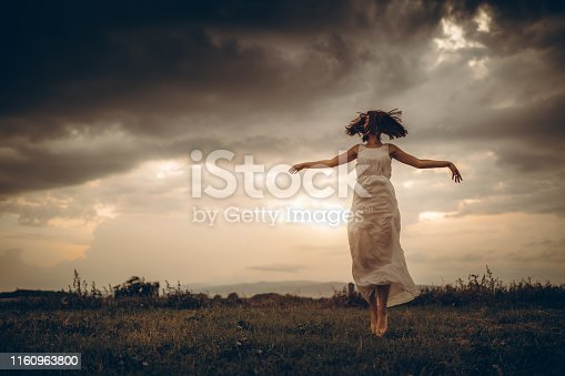 Young caucasian woman levitating in grass field.