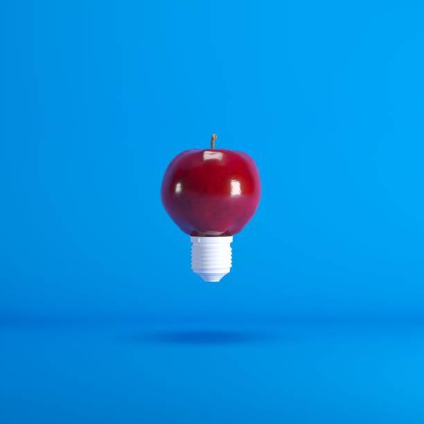 Levitating Lightbulb Apple floating on blue background color. minimal idea concept. stock photo