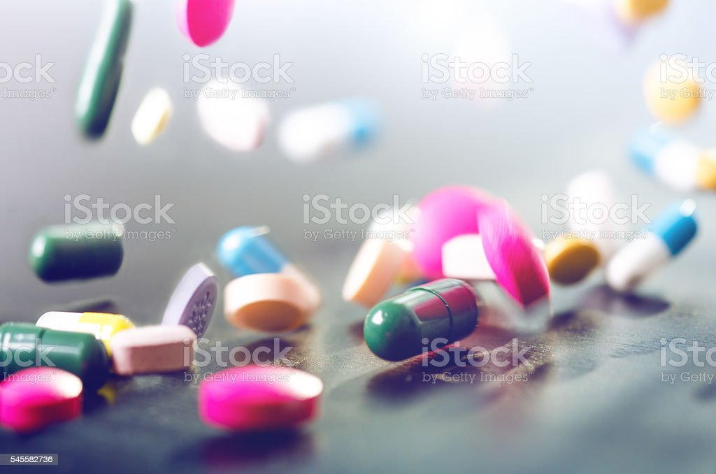 Levitation of pills on a black background - Photo