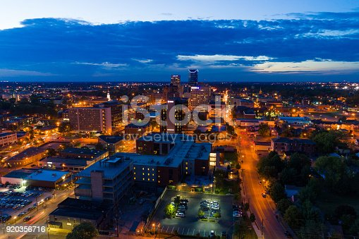 Downtown Lexington aerial view at dusk with illuminated streets and a partly cloudy sky.
