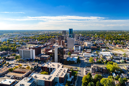 Aerial view of Downtown Lexington, Kentucky with a blue sky with clouds and the metropolitan area cityscape in the background.