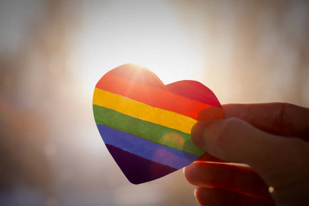 lgbt rights concept, hand holds a heart painted like a LGBT flag, silhouetted against sun lgbtqi pride event stock pictures, royalty-free photos & images
