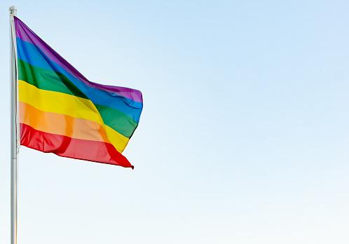 lgbti concept: lgbt rainbow flag on a pole waving in the wind