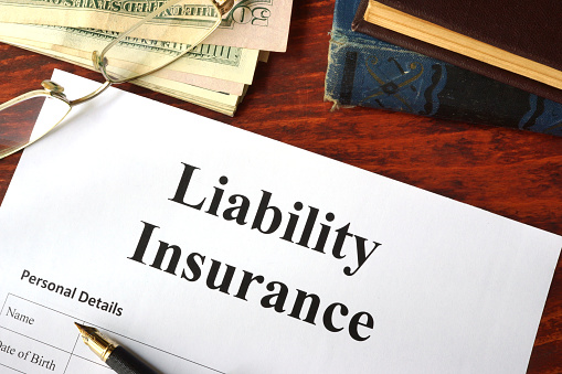 Liability insurance on a wooden table with glasses.