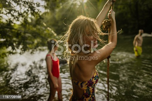 Photo of a young woman who is spending hot summer day with her friends on the river, swinging on a rope that looks like liana