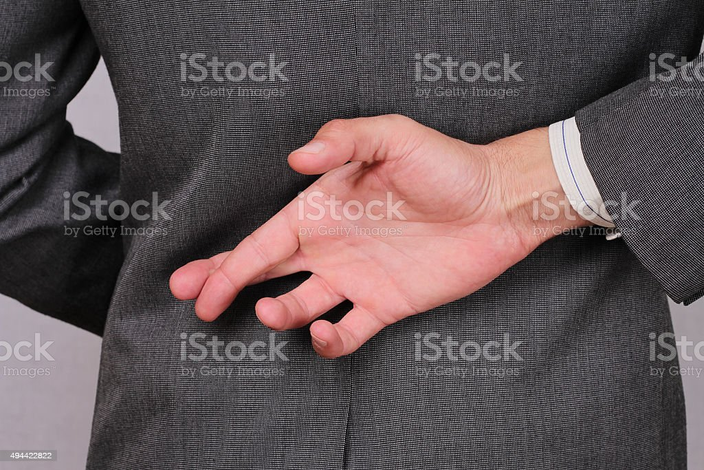 Liar businessman with crossed fingers at back . stock photo