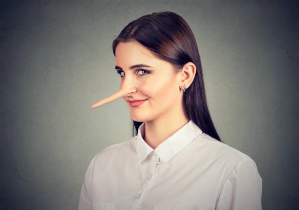 lügner schlau lustig aussehende junge frau - wahre lügen stock-fotos und bilder