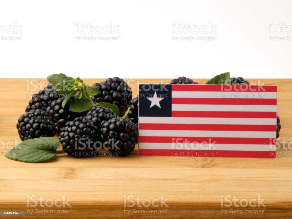Liberian flag on a wooden panel with blackberries isolated on a white background stock photo