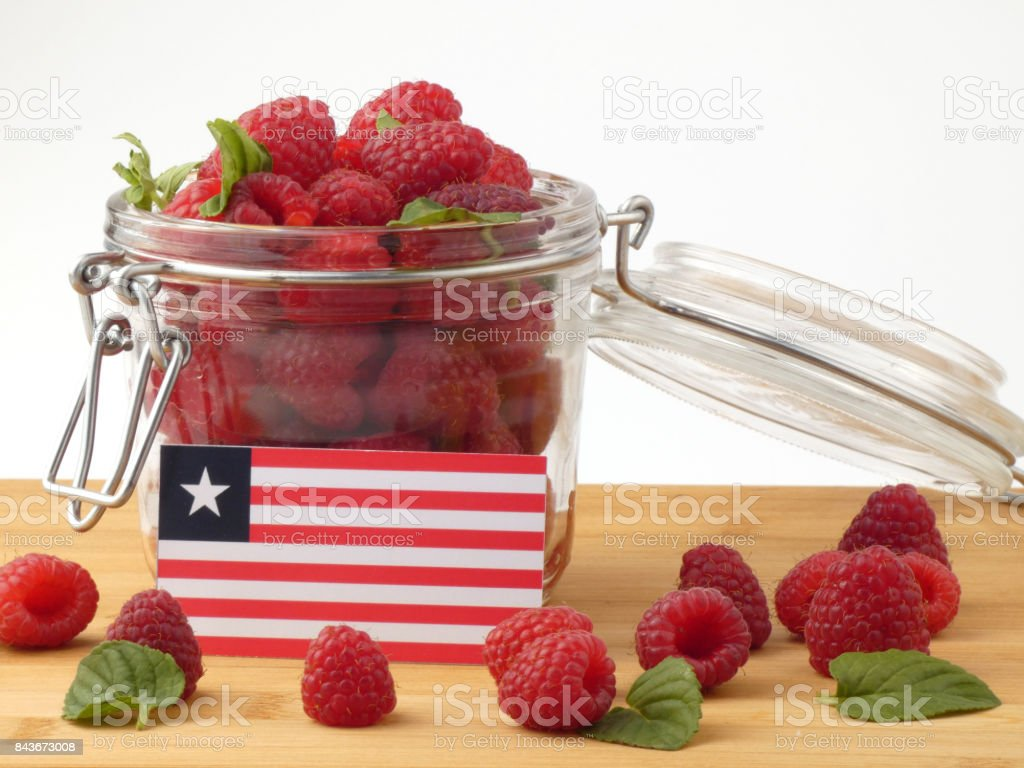 Liberian flag on a wooden panel with raspberries isolated on a white background stock photo