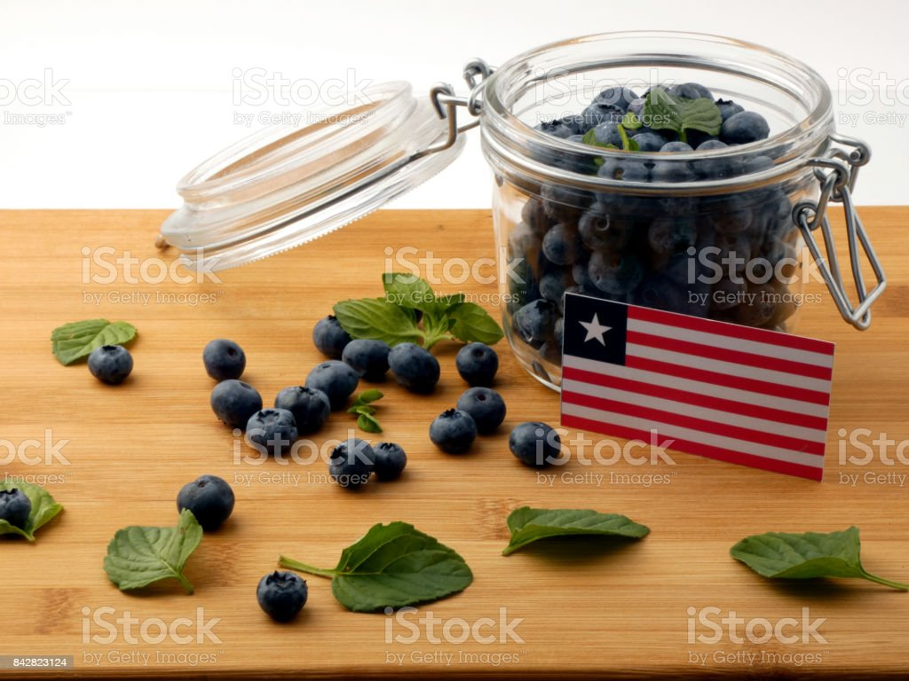 Liberian flag on a wooden plank with blueberries isolated on white stock photo