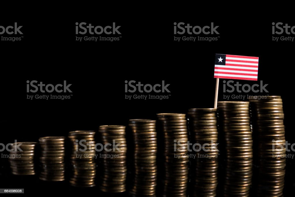 Liberian flag with lot of coins isolated on black background stock photo