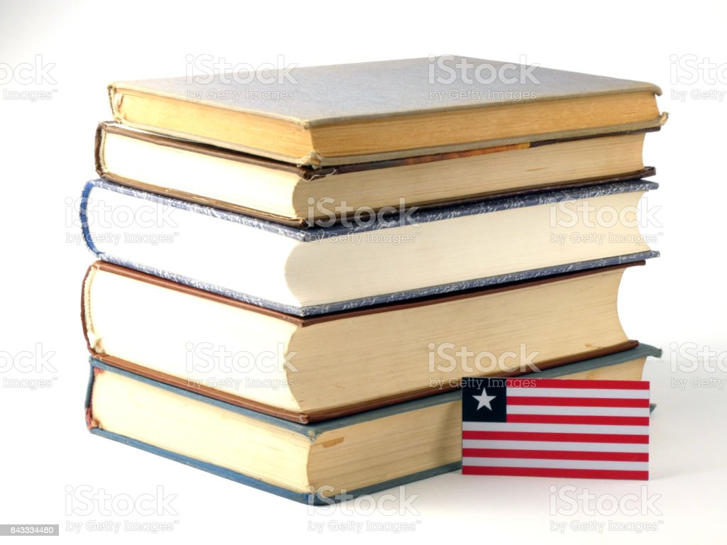 Liberian flag with pile of books isolated on white background stock photo